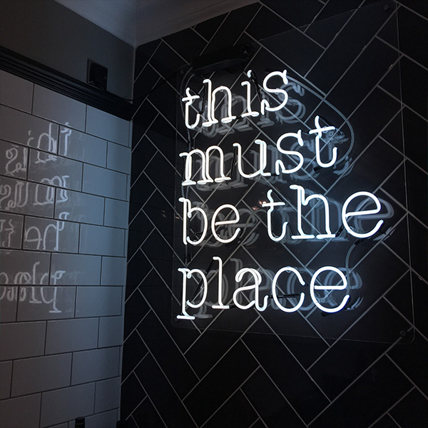 Neon light sign white this must be the place