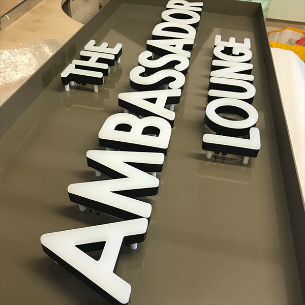 faux neon sign The Ambassador Lounge white